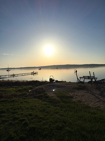Early morning bike ride with sunrise over a calm West Bay with a few early boat moorings. Photo by Russ VanHouzen.