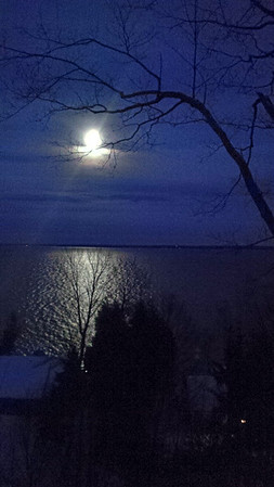 The moon shines over West Grand Traverse Bay. Photo by JJ Johnson.