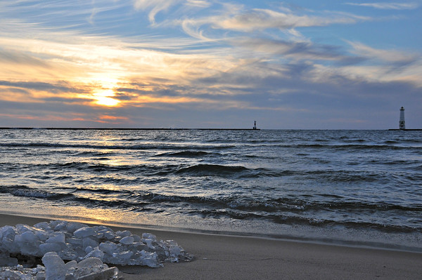 The sun sets over an icy Frankfort beach on Lake Michigan. Photo by Heather Spaleny.