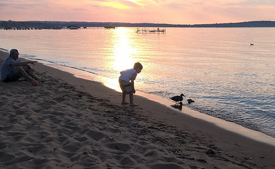 Visitors feeding a duck family at sunset on East Bay. Photo by Susan Pepsin.