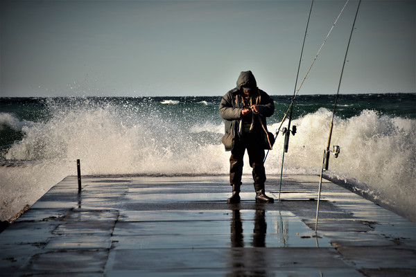 A fisherman turns away from the waves at a Frankfort pier. Photo by Jennifer Mikowski.