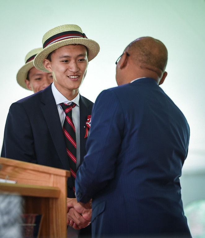 . Kevin Gu Xiao, left, is presented with the President Theodore Roosevelt Award by Headmaster, Temba T. Maqubela, during The Groton School graduation ceremony Sunday.  His twin brother, Michael, also received the same award.   SUN/Scot Langdon