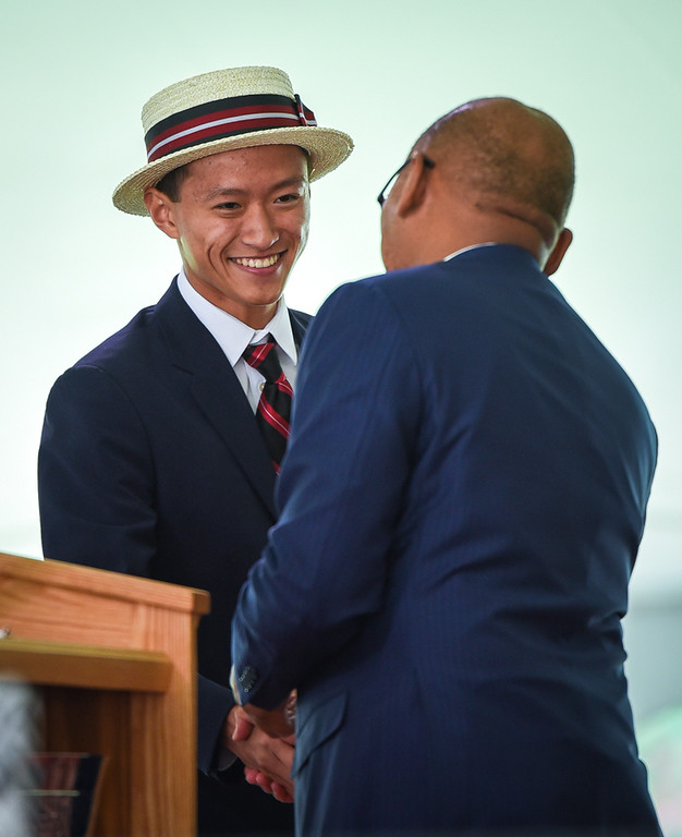 . Michael Gu Xiao, left, is presented with the President Theodore Roosevelt Award by Headmaster, Temba T. Maqubela, during The Groton School graduation ceremony Sunday.  His twin brother, Kevin, also received the same award.   SUN/Scot Langdon