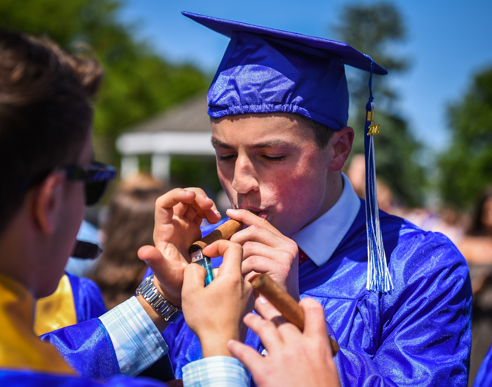 . Wilmington High School graduate, Kyle Bolas, celebrates his milestone with friends and a cigar Sunday after graduation ceremonies.  SUN/Scot Langdon