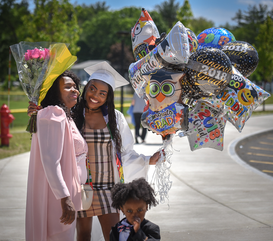 . Lessita Louis, right, celebrates her graduation day with her family and her mother, left, after Wilmington High School ceremonies Sunday afternoon.  Louis is starting at Framingham State University in the fall studying biology/premed.  SUN/Scot Langdon