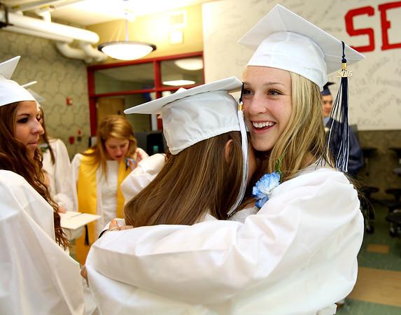 KEN YUSZKUS/Staff photo. Graduates Anne Whelan, left, and Chrisine Brennick hug each other before the start of the Hamilton-Wenham graduation.    6/07/15