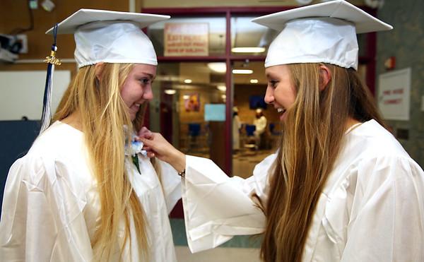 KEN YUSZKUS/Staff photo. Graduates Kristin Hefferman, left, has a carnation pinned on by Brenna Thompson before the start of the Hamilton-Wenham graduation.    6/07/15