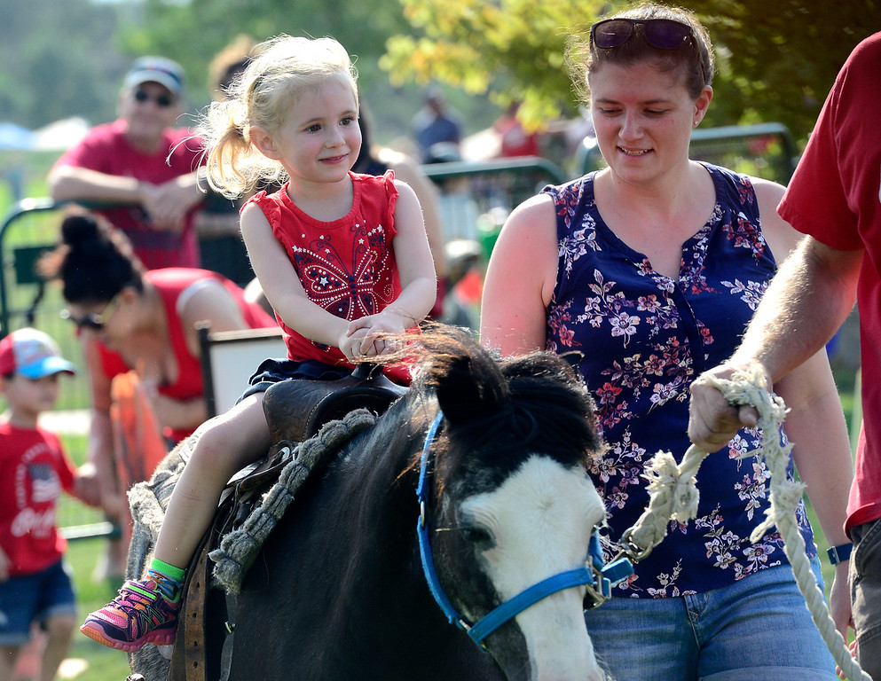 . Ryah Baker, 3, rides Romeo from the MNC Farm with the help of her mom Tenesha at the Great American Picnic at the Broomfield County Commons on Wednesday July 4. For more photos go to broomfieldenterprise.com.  Paul Aiken / Staff Photographer July 4, 2018