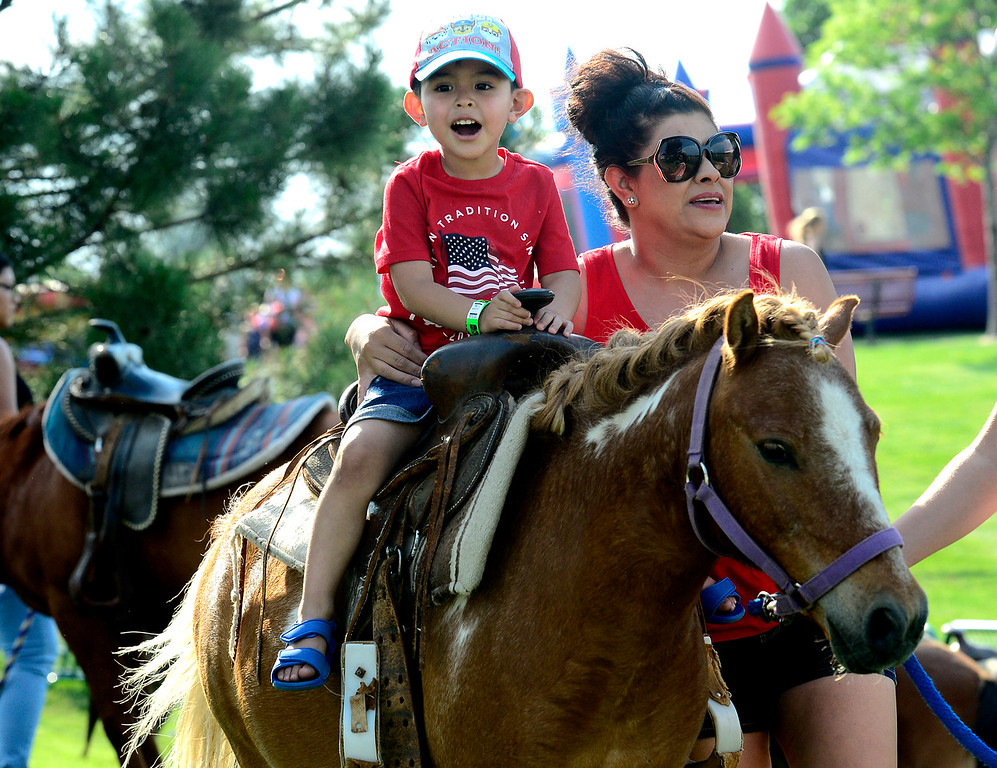 . Mateo Almanza rides Noodle from the MNC Farm with the help of his mom Mayra at the Great American Picnic at the Broomfield County Commons on Wednesday July 4. For more photos go to broomfieldenterprise.com.  Paul Aiken / Staff Photographer July 4, 2018