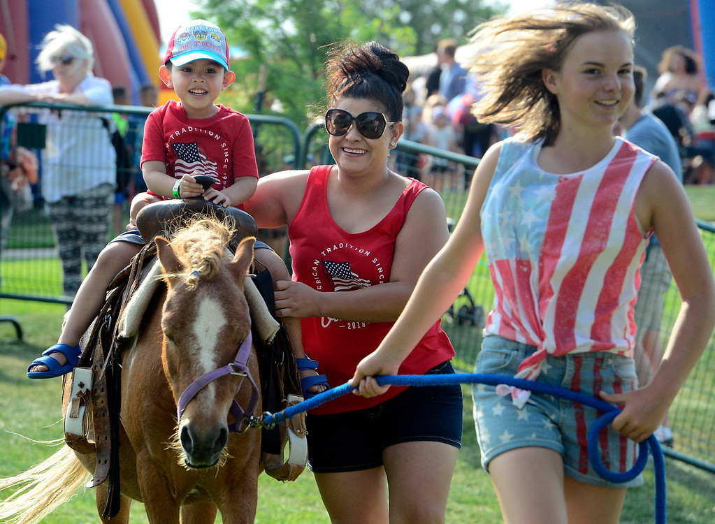 . Mateo Almanza rides Noodle led by Kendra Graves from the MNC Farm with the help of his mom Mayra at the Great American Picnic at the Broomfield County Commons on Wednesday July 4. For more photos go to broomfieldenterprise.com.  Paul Aiken / Staff Photographer July 4, 2018