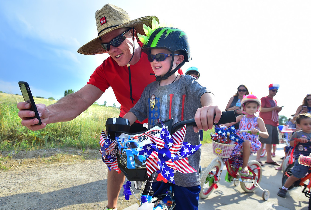 . Bruce Hawkins gets a photo with his son Max, 7, before the Bike Parade at the Great American Picnic at the Broomfield County Commons on Wednesday July 4. For more photos go to broomfieldenterprise.com.  Paul Aiken / Staff Photographer July 4, 2018