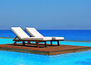 Lounge chairs on a Rhodes island De Luxe Hotel swimming pool, by the sea