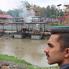 Pashupatinath Temple in the city of Kathmandu. The temple is a Hindu place of worship. Behind Nitin's head, families are performing traditional cremation ceremonies of family members that have passed. The remaining ashes are placed in the Bagmati River (pictured) as part of tradition. The Bagmati River is seen as a holy river, like the Ganges in India. Our guide said photos were welcome.