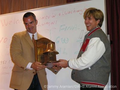 Lincoln Principal Barnaby Payne hands the Bell Trophy to Washington Principal Ericka Lovrin