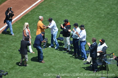 Jan Dravecky, Dave Dravecky and Kevin Mitchell shaking hands, Will Clark, Bob Knepper, Scott Garrelts, Willie McCovey and Larry Baer