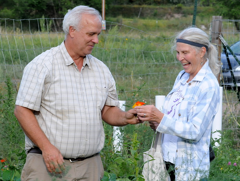 Dave McMurtrey, owner of Glade Road Orchard west of Loveland, gives a nasturtium, an edible flower, to customer Cathe Read to sample on Wednesday, Aug. 22, 2018.  (Photo by Craig Young / Loveland Reporter-Herald)