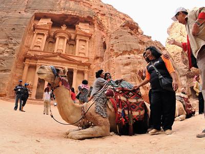 Touristen bewundern ein Dromedar vor dem Schatzhaus in Petra. Die berühmte Nabatäerstadt Petra, Jordaniens größte touristische Attraktion, liegt geheimnisvoll verborgern inmitten einer Felslandschaft