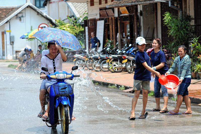"""Beim traditionellen laotischen Neujahrsfest besprengen sich die Buddhisten gegenseitig mit Wasser, um die Sünden des alten Jahren abzuwaschen. In Luang Prabang ist daraus ein ausgelassenes und friedliches Spektakel geworden, bei dem sich Bewohner und Besucher in den Straßen nassspritzen.  Bei jungen Rucksacktouristen aus Australien, Europa und USA hat sich das Fest längst zum Geheimtipp entwickelt. Jedes Jahr strömen mehr """"Backpacker"""" zur Wasserschlacht in die ehemalige Königsresidenz Luang Prabang."""