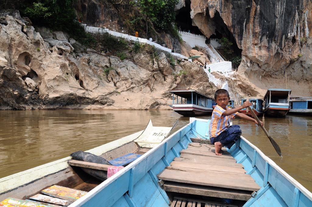 Mit dem Boot auf dem Mekong; im Hintergrund der Aufgang zu den Höhlen von Pak Ou, die unzählige Buddha-Figuren beherbergen