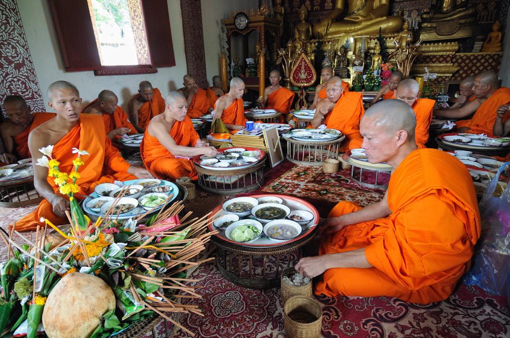 Aus Luang Prabang eingeladene Mönche essen im Tempel; Feierlichkeiten zur Einweihung einer Stupa am Tempel im kleinen Ort Ban Naxao in der Nähe von Luang Prabang