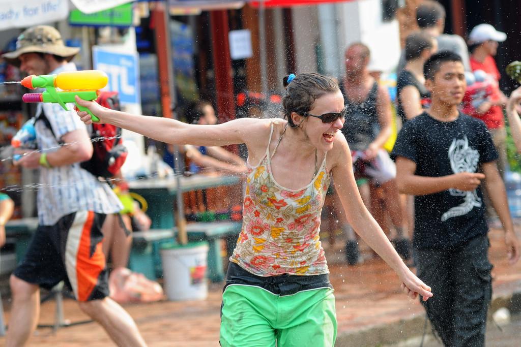 """Wasserschlacht auf der Th Sisavangvong, der zentralen Straße in Luang Prabang mit den meisten Cafés und Touranbietern / Reisebüros. <br /> Beim traditionellen laotischen Neujahrsfest besprengen sich die Buddhisten gegenseitig mit Wasser, um die Sünden des alten Jahren abzuwaschen. In Luang Prabang ist daraus ein ausgelassenes und friedliches Spektakel geworden, bei dem sich Bewohner und Besucher in den Straßen teilweise mit überdimensionalen Hochdruck-Wasserpistolen nassspritzen, Kolonnen von Pickups mit großen Wasserbottichen für Nachschub sorgen und jeder, der sich vor die Tür wagt, triefend nass zurück kommt. <br /> Bei jungen Rucksacktouristen aus Australien, Europa und USA hat sich das Fest zum Geheimtipp entwickelt. Jedes Jahr strömen mehr """"Backpacker"""" zur Wasserschlacht in die ehemalige Königsresidenz Luang Prabang."""