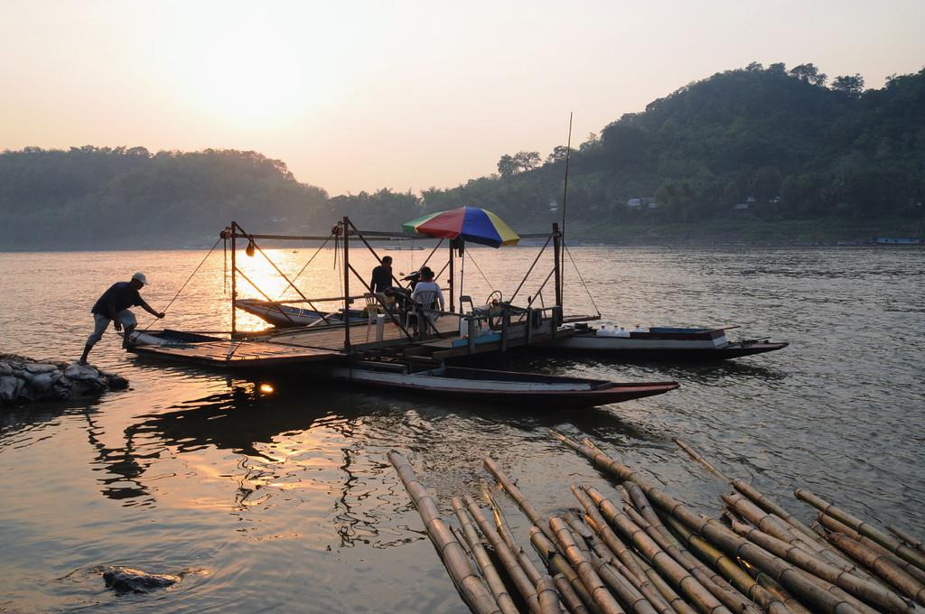 Fähre über den Mekong im goldenen Licht des Sonnenuntergangs an der Slowboat-Anlegestelle