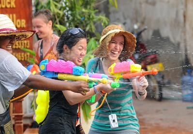"""Wasserschlacht auf der Th Sisavangvong, der zentralen Straße in Luang Prabang mit den meisten Cafés und Touranbietern / Reisebüros. Beim traditionellen laotischen Neujahrsfest besprengen sich die Buddhisten gegenseitig mit Wasser, um die Sünden des alten Jahren abzuwaschen. In Luang Prabang ist daraus ein ausgelassenes und friedliches Spektakel geworden, bei dem sich Bewohner und Besucher in den Straßen teilweise mit überdimensionalen Hochdruck-Wasserpistolen nassspritzen, Kolonnen von Pickups mit großen Wasserbottichen für Nachschub sorgen und jeder, der sich vor die Tür wagt, triefend nass zurück kommt.  Bei jungen Rucksacktouristen aus Australien, Europa und USA hat sich das Fest zum Geheimtipp entwickelt. Jedes Jahr strömen mehr """"Backpacker"""" zur Wasserschlacht in die ehemalige Königsresidenz Luang Prabang."""