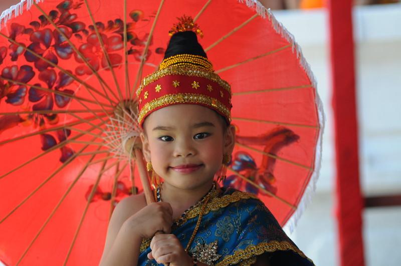 Kind im Wat May. Für die Feierlichkeiten zum laotischen Neujahrsfest haben viele Eltern ihre Kinder herausgeputzt. Der Höhepunkt des laotischen Neujahrsfests im April in Luang Prabang ist die große Parade zwischen dem Wat May und dem Wat Xieng Thong