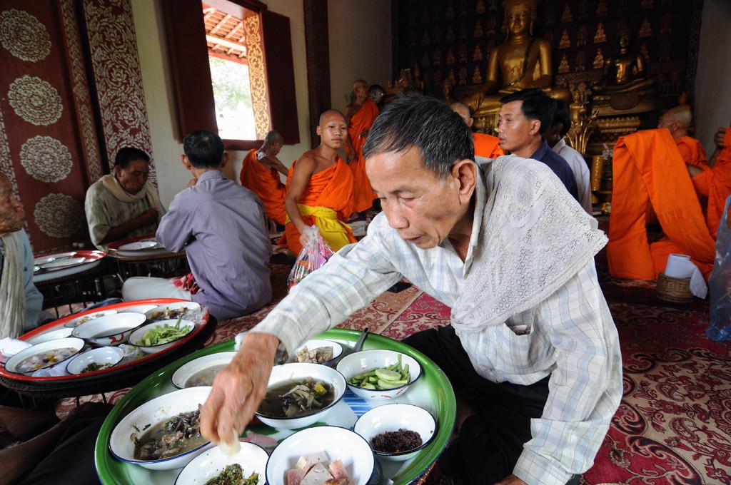 Einheimische und aus Luang Prabang eingeladene Mönche essen im Tempel; Feierlichkeiten zur Einweihung einer Stupa am Tempel im kleinen Ort Ban Naxao in der Nähe von Luang Prabang