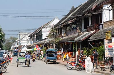 Tuk Tuk (Auto- oder Motorradrikscha in Südostasien) auf der Th Sisavangvong, der zentralen Straße in Luang Prabang mit den meisten Cafés und Touranbietern / Reisebüros