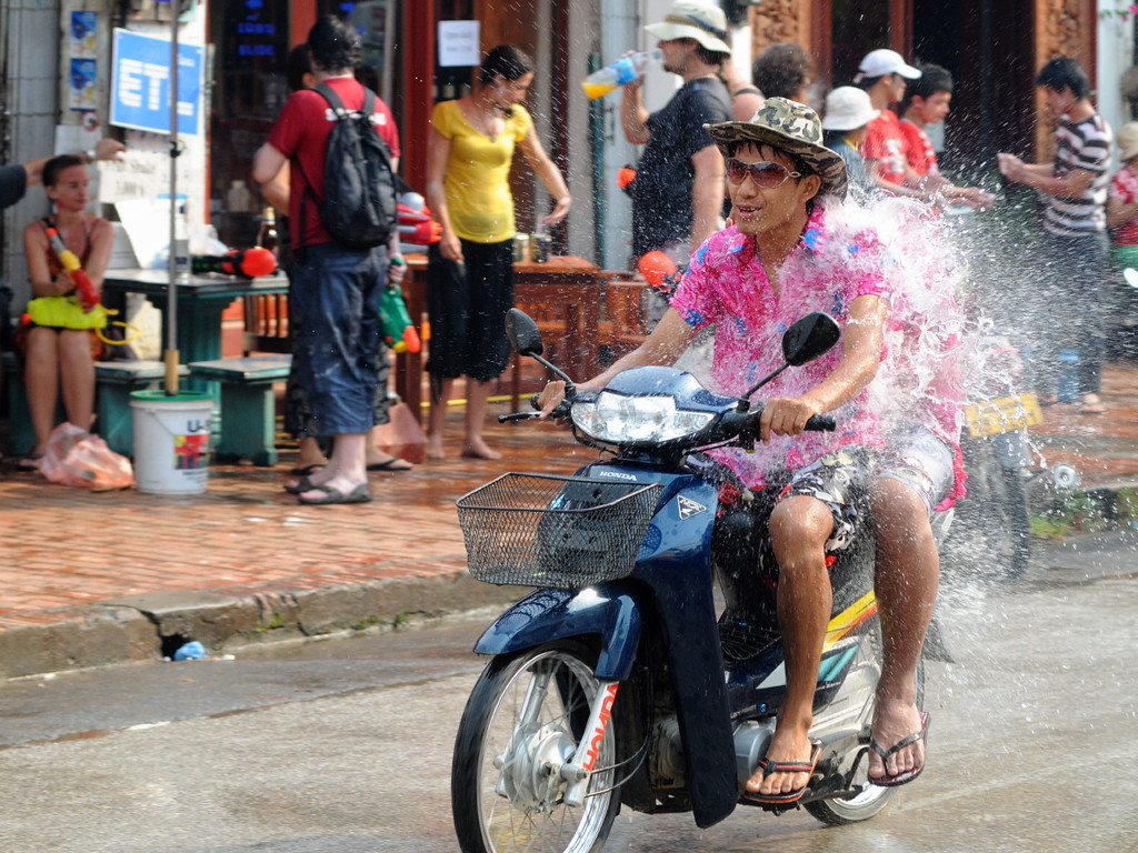 """Wasserschlacht auf der Th Sisavangvong, der zentralen Straße in Luang Prabang mit den meisten Cafés und Touranbietern / Reisebüros. Beim traditionellen laotischen Neujahrsfest besprengen sich die Buddhisten gegenseitig mit Wasser, um die Sünden des alten Jahren abzuwaschen. In Luang Prabang ist daraus ein ausgelassenes und friedliches Spektakel geworden, bei dem sich Bewohner und Besucher in den Straßen teilweise mit überdimensionalen Hochdruck-Wasserpistolen nassspritzen, Kolonnen von Pickups mit großen Wasserbottichen für Nachschub sorgen und jeder, der sich vor die Tür wagt, triefend nass zurück kommt. <br /> Bei jungen Rucksacktouristen aus Australien, Europa und USA hat sich das Fest zum Geheimtipp entwickelt. Jedes Jahr strömen mehr """"Backpacker"""" zur Wasserschlacht in die ehemalige Königsresidenz Luang Prabang."""