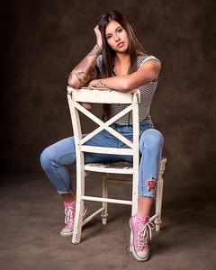 Jeune femme sur une chaise en studio.