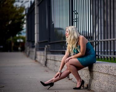 Modèle assise sur un muret.