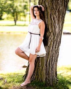 Jeune femme appuyée à un arbre.