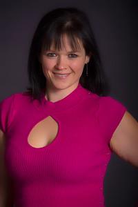 Femme au joli sourire portant un chandail rose.