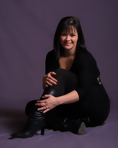 Femme souriante portant des bottes en noir.