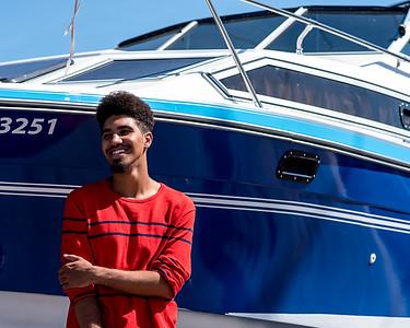 Homme noir posant devant un yacht.