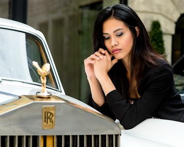 Jolie brunette devant une auto de luxe.