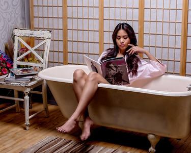 Jolie brunette aux longs cheveux relaxant au bain.