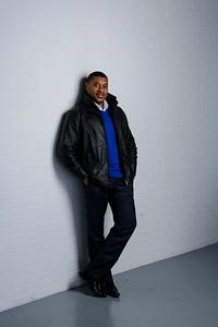 Bel homme noir en veste de cuir appuyé à un mur.