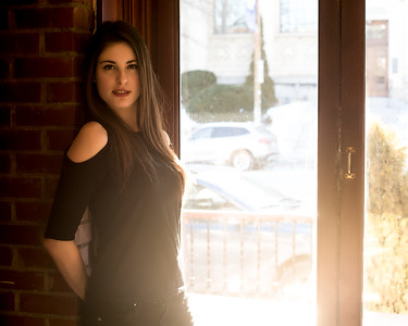 Jolie brunette près d'une fenêtre d'un café.