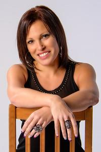 Portrait rapproché d'une brunette posant sur une chaise en studio.