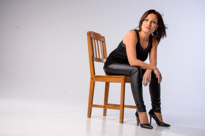 Portrait d'une jeune femme posant sur une chaise en studio.