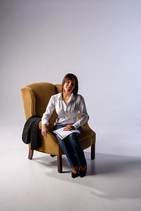 Jeune femme souriante assise au fauteuil.