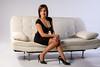 Belle femme sur un canapé blanc en robe noire.