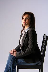 Jolie femme assise en studio, regard au loin.