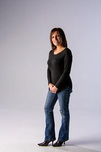 Jolie jeune femme posant debout en jeans.
