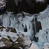 La cascade gelée de la Sauffraz devant un sommet dont ... je ne connais toujours pas le nom, en fait.<br /> Il me semble que c'est la pointe de Sales (mais pas sur!)<br /> <br /> C'était une journée assez impressionnante, seuls dans ce paysage gelé. On a voulu monter en voiture sur une route théoriquement fermée en hiver (il n'avait pas neigé depuis un mois) pour gagner du temps et du dénivelée ... A forces de glissades non maitrisées vers les sapins .. on s'est arrêtés au milieu de nulle part au bord de la route sur une pente enneigée. <br /> <br /> On a mis les raquettes qu'on a laissés un peu plus loin dans un arbuste; et on est allé voir la cascade de Sales dans un silence inquiétant. <br /> Alexandre marche vite. J'ai du mal à suivre au début. <br /> <br /> Au retour, on descend vers la Sauffraz et la Pleureuse, très gelées; seulement un petit filet d'eau. <br /> Alexandre disparait (?!) je me rend compte qu'il est passé sous une partie de la cascade, dans un drôle de trou derrière les stalactites. Je le rejoint, j'ai la trouille, je viens de voir par terre un bout de glace brisé d'environ ma taille qui à l'air de venir du haut.<br /> <br /> A peine dans l'anfractuosité, on entend un énorme bruit et des choses tomber . Hum. Pas sur nous heureusement mais ... bon.<br /> <br /> Copyright : Ambre de l'AlPe