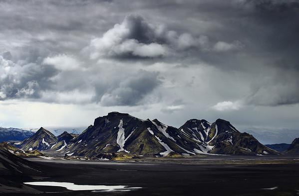 Panoramique magistral. Les montagnes nous encerclent, cônes moussus émergeant des ténèbres du désert. Les nuages font concurrence au sol, s'obscurcissant de plus en plus. Bientôt ils se lanceront avec leurs cordes trempées à l'abordage de la Terre, et il pleuvra à verse… Derrière, des monts couleur caramel closent l'horizon. Sur les contreforts des formes de gardiens se dessinent. Des gargouilles de pierre, fantomatiques, nous observent. <br /> <br /> Je redescends en courant du mirador. Un chemin, des pierres. Un tapis de mousse. De l'herbe. La crête, rampe qui serpente jusqu'en bas. Un névé grisâtre me permet de glisser en style libre alors que la pluie se change en grêle puis en grésil neigeux. Les nuages colériques se déchargent sur les environs, qui blanchissent en même temps qu'eux. <br /> <br /> Copyright : Ambre de l'AlPe