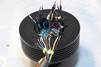 Ik besloot om de kabel aan de CCD kop kant ongeveer 10 cm. in te korten en opnieuw te solderen. Echter na openen van de CCD kop bleek dat er erg weinig ruimte is om de draadjes weer op de print te solderen. De print is overigens vastgekit in de kop dus die kon er ook niet uit worden gehaald. Ik heb daarom de draden die uit de print komen zo kort mogelijk afgeknipt en de draden van de kabel hier weer aangesoldeerd. Om het soldeerpunt heb ik netjes een stukje krimpkous gekrompen.  Hier een foto van de afgeknipte draden.